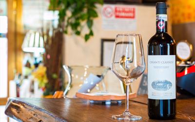 Primo piano di un bicchiere su un tavolo con una bottiglia di vino