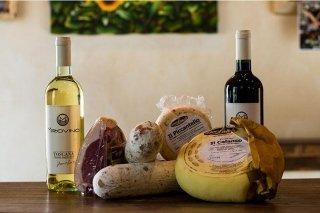 due bottiglie di vino rosso e bianco, formaggi e salumi