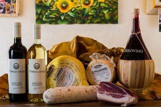 Primo piano di una damigiana di vino rosso, una bottiglia di vino bianco, forme di formaggi e salumi