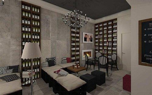 Interno del locale con divanetti,una lampada e degli scaffali con bottiglie di vino