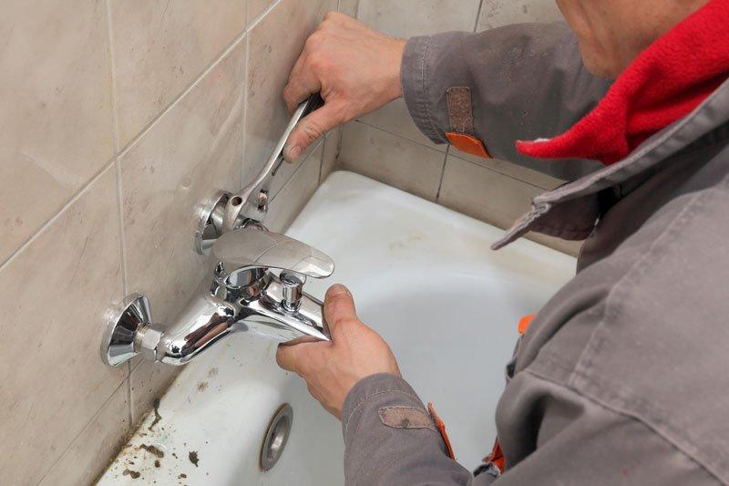 un idraulico svita un rubinetto