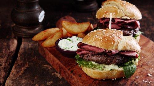 hamburger con patatine e formaggio sopra un tagliere