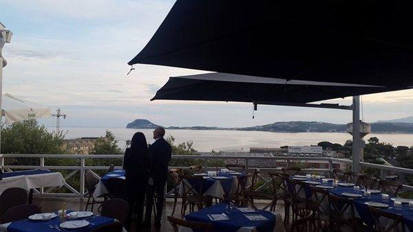 due clienti guardano il paesaggio dalla zona esterna del ristorante