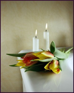 Red and yellow tulips on a table next to 2 white burning candles
