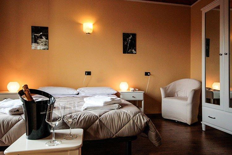 una camera d'albergo con un tavolino con due bicchieri, dello champagne