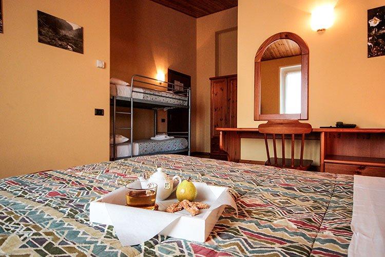 una stanza d'albergo con un letto matrimoniale e un letto a castello