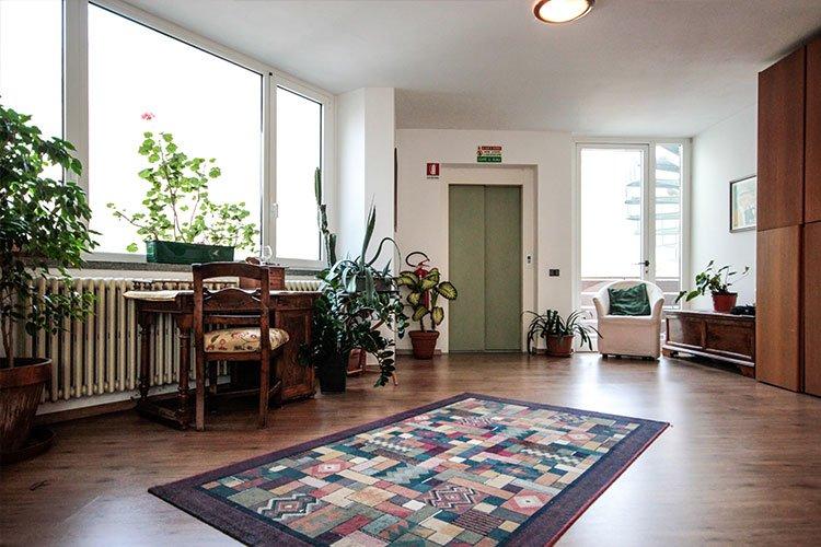un piano di un albergo con un tavolino con una sedia e dei vasi con delle piante