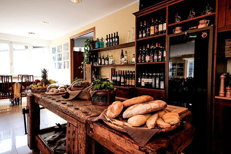 un tavolo con un cesto di pane e delle bottiglie di vino negli scaffali