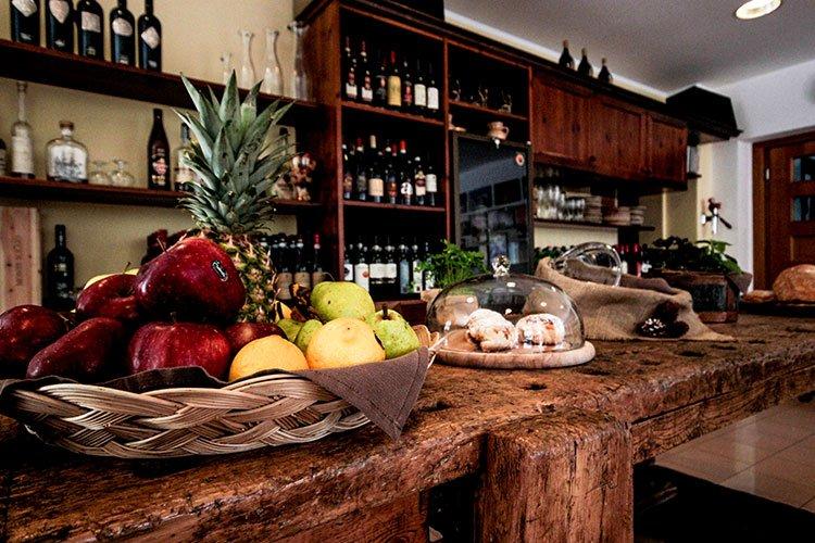 un tavolo con un cesto di mele e delle bottiglie di vino negli scaffali