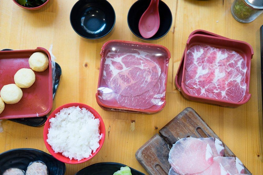 salumi su piatti rossi e su tagliere, ciotola di riso e ciotole per salsa di soia su tavolo di legno