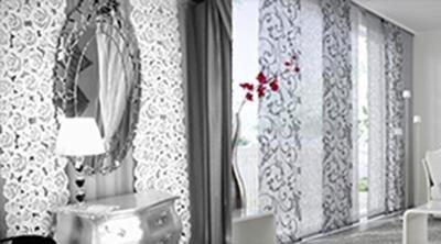 Delle tende dritte di color bianco e grigio con dei disegni a fiori
