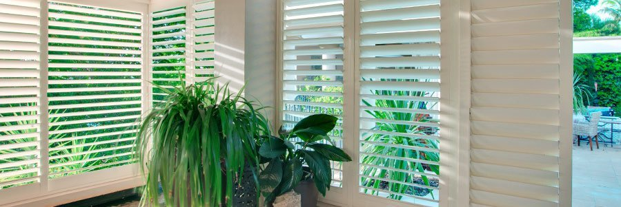 sunroom shutters looking out on green backyard