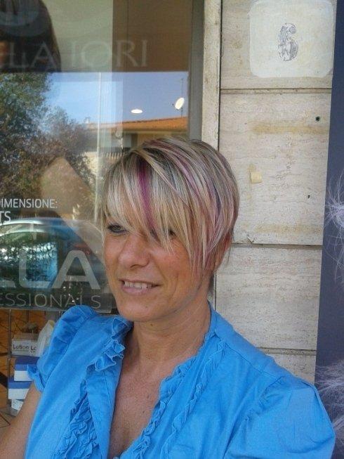 cliente fuori dal negozio con i capelli corti biondi scalati lisci e meches viola