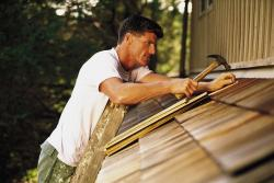 Roofer putting wooden shingles on roof