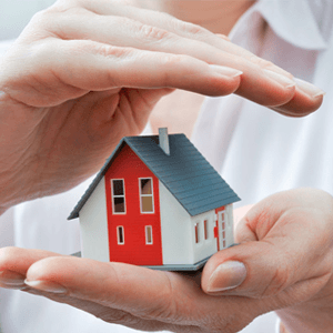 A hand holding a toy house