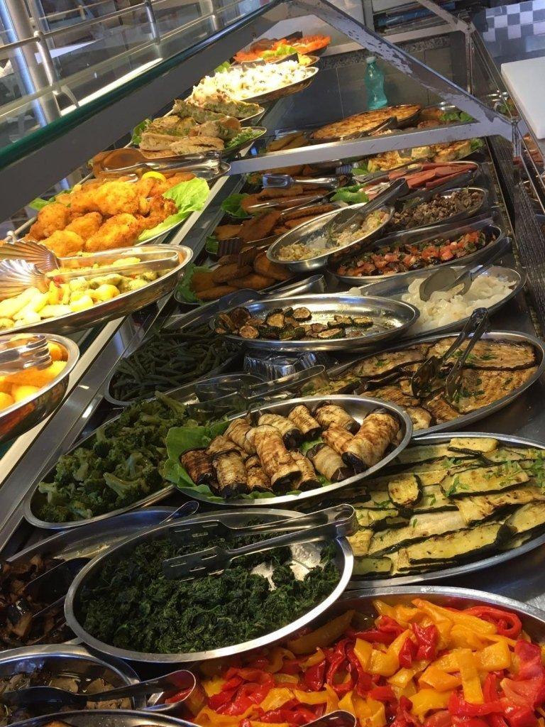 banco con vassoi di verdure grigliate e piatti di carne e pesce fritti