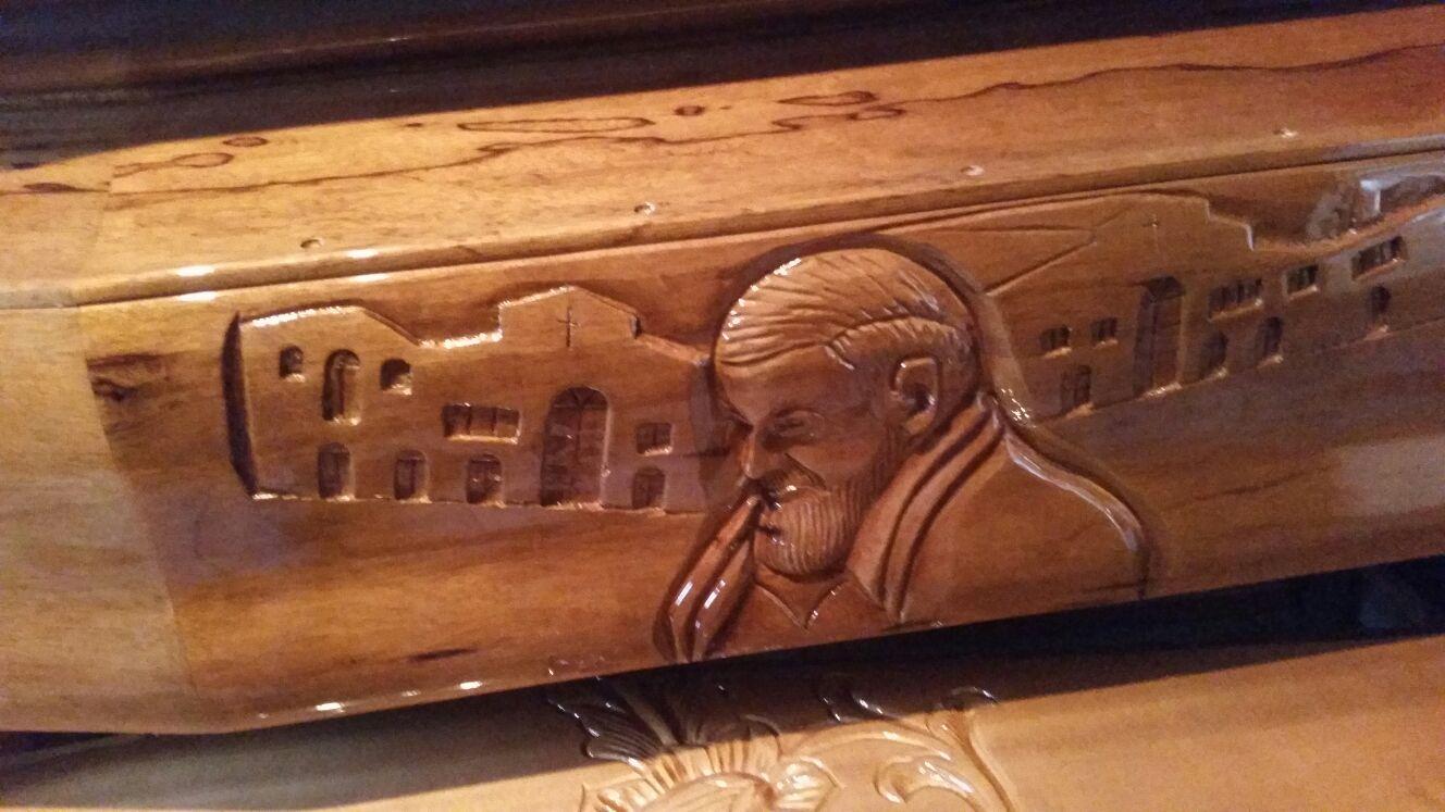 Volto di Padre Pio intarsiato su un cofano in legno