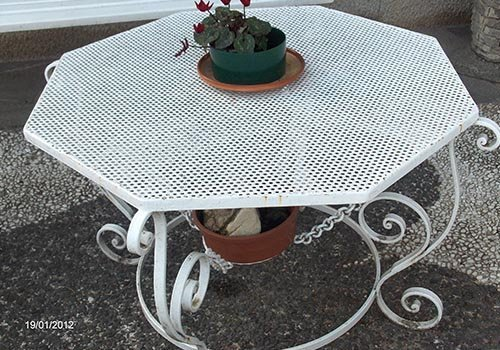 un tavolo in ferro battuto di color bianco con sopra un vaso di fiori