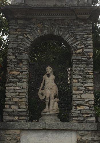 una statua in un giardino sotto un arco in pietra