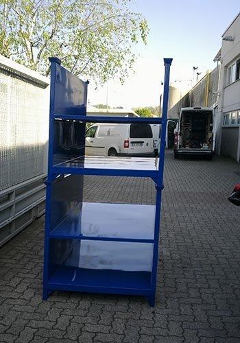 uno scaffale blu all'esterno e dei furgoni