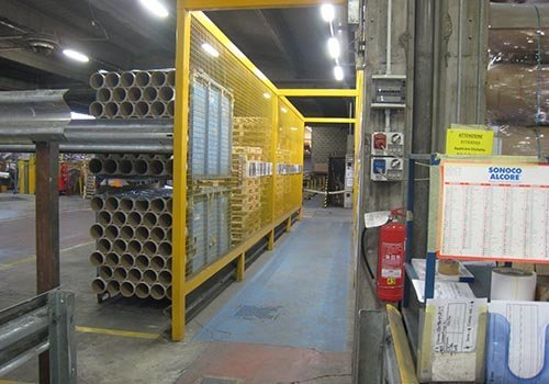 una struttura in ferro reticolata di color giallo in un magazzino