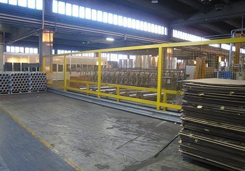 una struttura di ferro gialla che funge da recinzione all'interno di una fabbrica