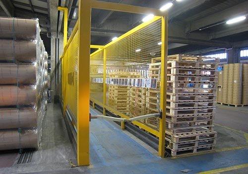 una struttura di ferro gialla e dei bancali in un magazzino