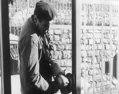 Foto in bianco e nero di un uomo lucidando un pezzo di metallo