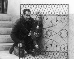 Un adulto e un bambino nascosti dietro di una griglia