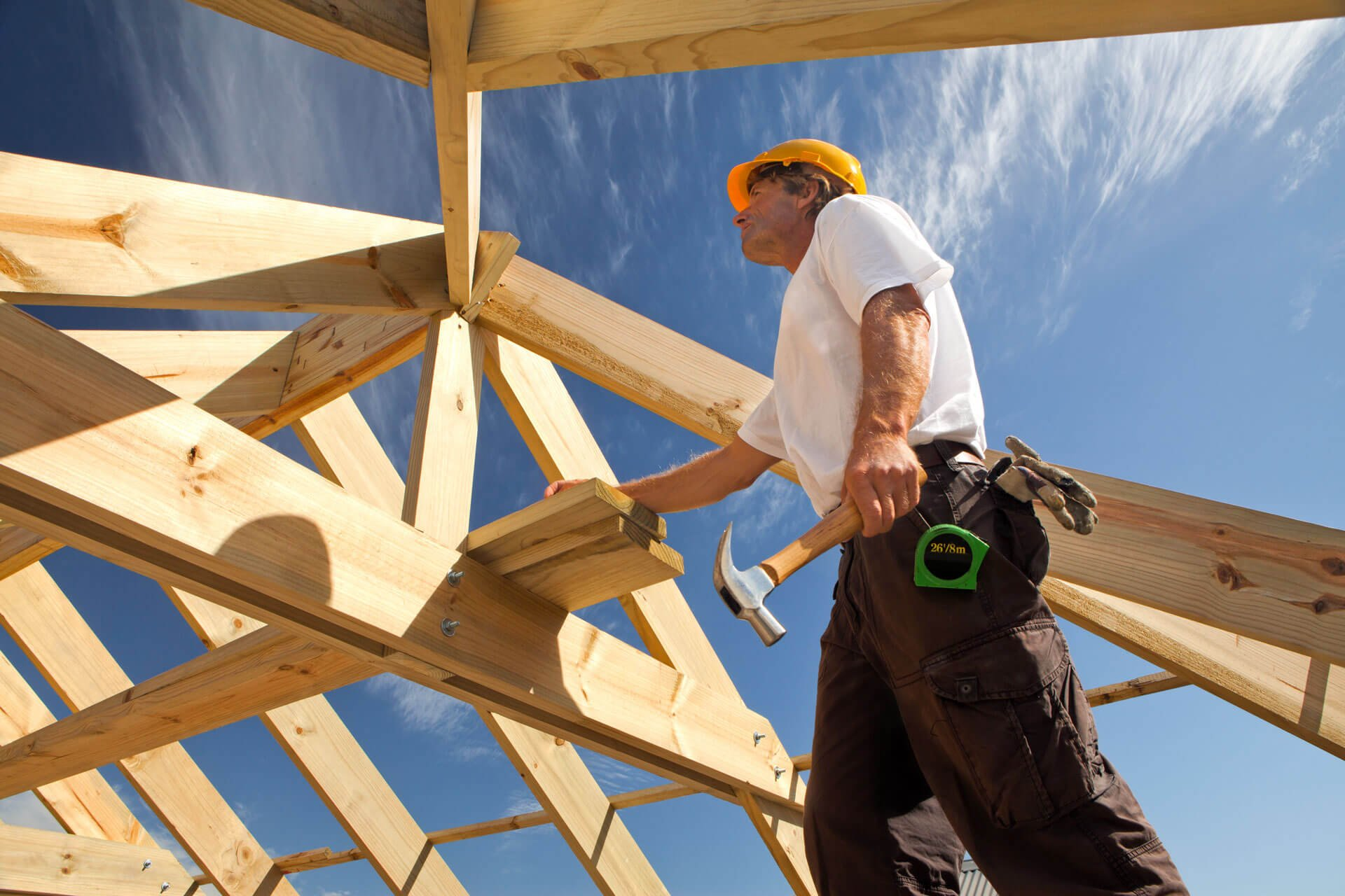 worker with hammer building roof