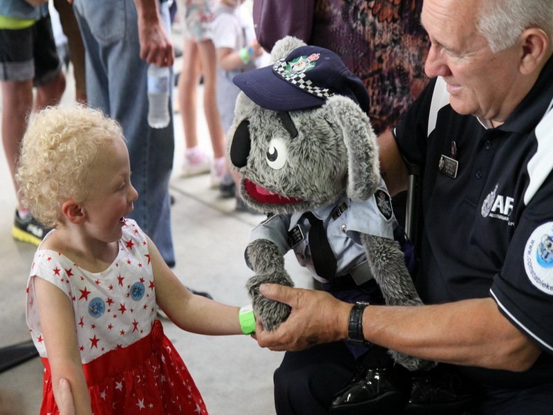 Kid being given a stuffed toy