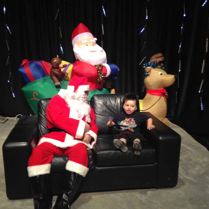 Santa sitting on sofa with a kid