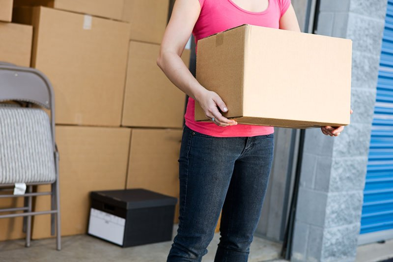Woman holding box by storage unit in Waterford