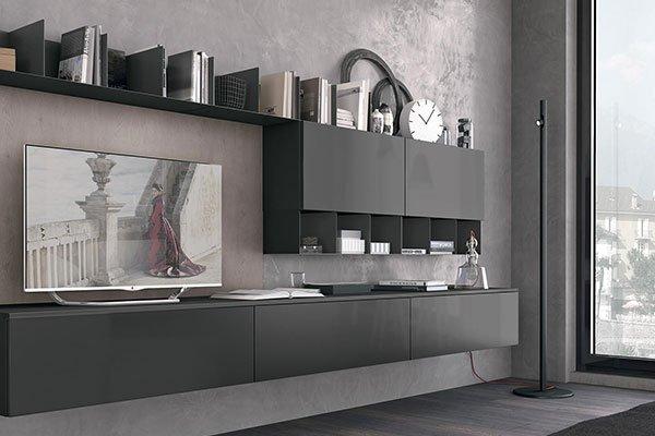 un mobile tv color grigio scuro con una tv e altri oggetti sopra