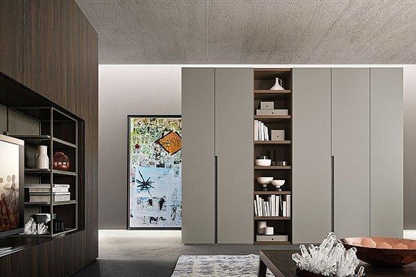 una sala con un armadio marrone con una tv sulla sinistra e di fronte un armadio grigio semi aperto