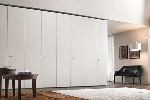 un armadio bianco in una sala e un tavolino marrone sulla sinistra