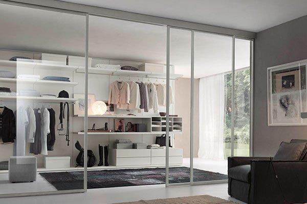 una porta di vetro e in fondo un mobile moderno di color bianco con dei vestiti appesi