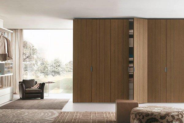 un armadio in marrone semi aperto in una stanza e sulla sinistra una poltrona