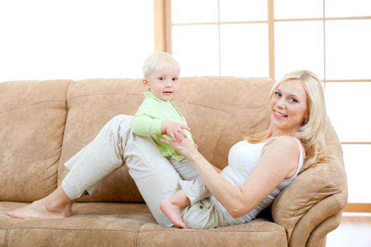 Mother with her baby having fun on clean sofa