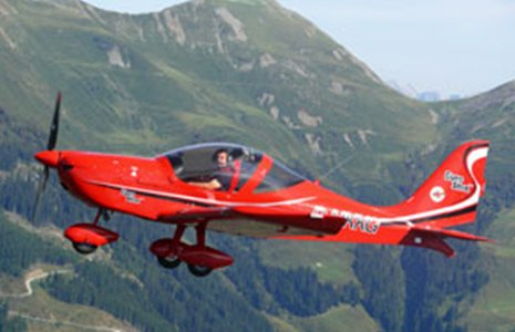 un aereo rosso e dietro delle montagne