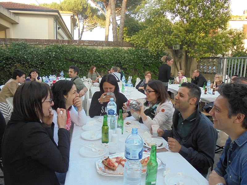 genitori ed educatori pranzano durante festa dell'asilo