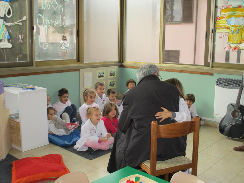 vescovo abbraccia una bambina