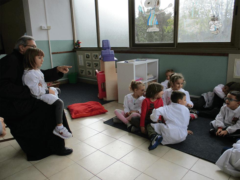 vescovo con bambina in braccio parla alla classe