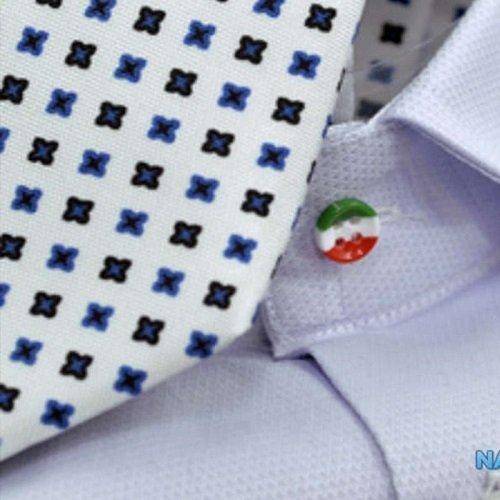 una stoffa bianca a disegni neri e blu e un bottone su una maglietta