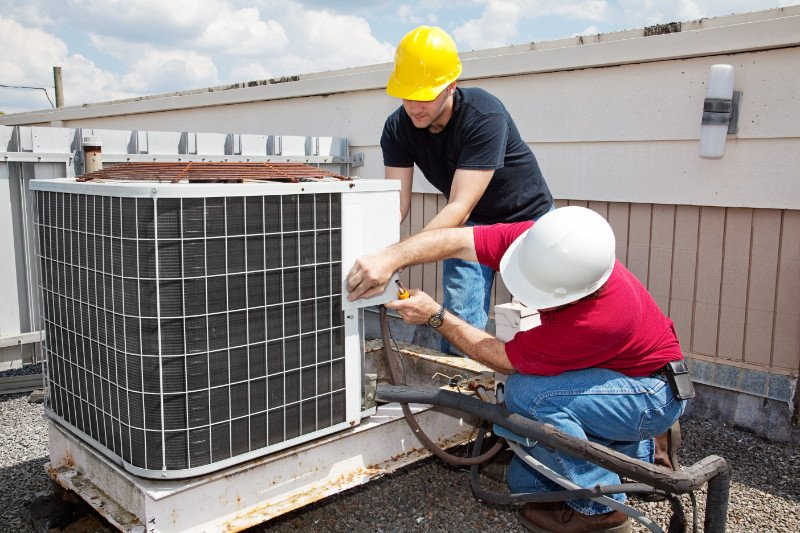 Two workers on the roof of a building working on the air conditioning unit