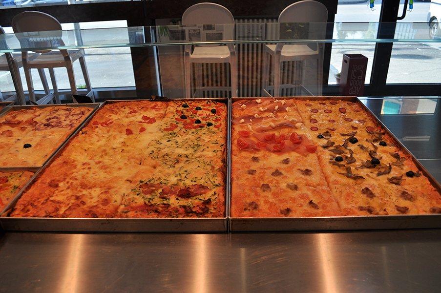 delle pizze e focacce esposte dentro a delle teglie