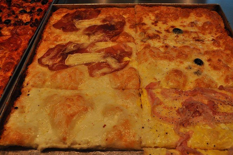 dei tranci di pizza di diversi tipi e gusti