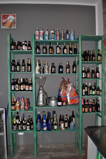 uno scaffale verde con delle bottiglie