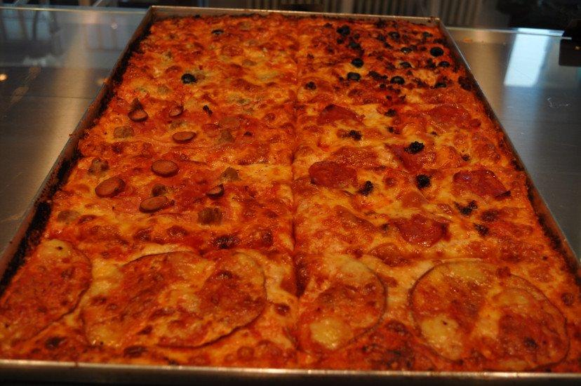una grossa teglia con dei tranci di pizza
