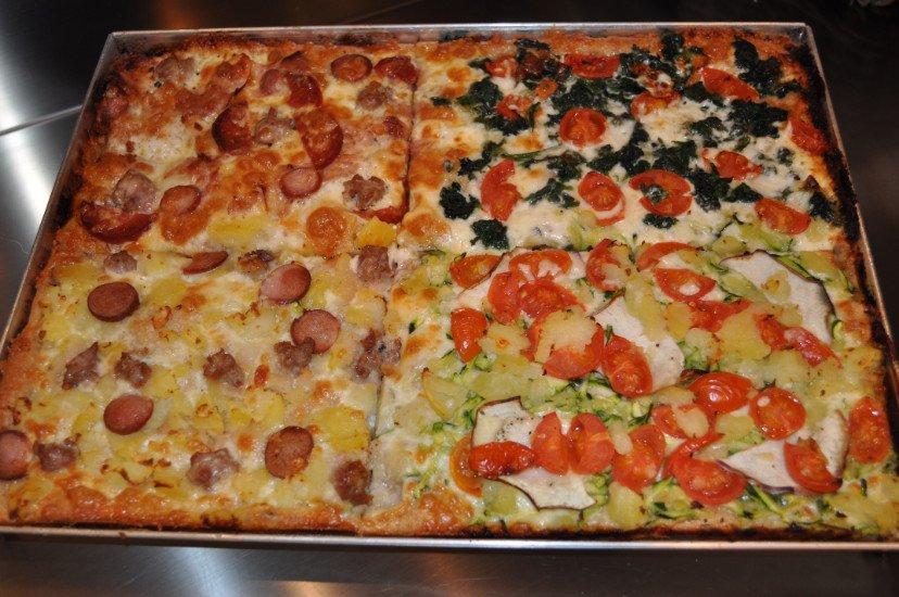 delle pizze farcite di diversi gusti dentro a una teglia
